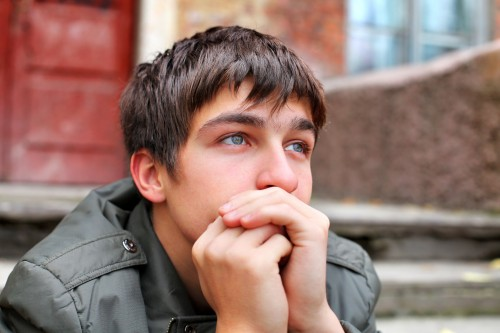 sad young man portrait on the old house background